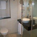 Bad: Blick auf Waschbecken, Toilette liegt links unterhalb der Handtücher