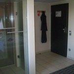 Blick auf Zimmertür/Garderobe, links neben dem Mantel befindet sich ein Kleiderschrank mit Safe