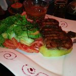 grilled alpaca. there are 2 slabs of meat one under the other. with avocado, tomato, cucumber