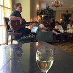 Having glass of wine and listen to singer in hotel lobby