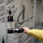 The shower door fully opened - barely more than a bottle of soda