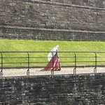 Actor in period dress walking along the bridge.