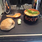 Delicious spring vegetable soup with noodles and pesto served with homemade wholemeal bread bun.