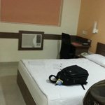 double room having 1 ton window AC, a LCD, a cupboard, an electronic kettle, a table, a chair