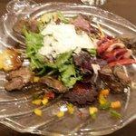 Salade de foies de volaille et copeaux de parmesan brochettes de tomates confites et magret fumé
