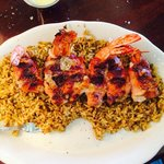 Jumbo bacon wrapped shrimp stuffed with jalapeño and cheese with dirty rice.