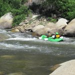 Watching kayakers come down the rapids from our private beach at our camp