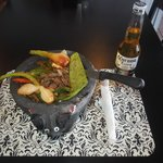 Fajitas Jalisco serve on a molcajete serve with rice, beans and tortillas