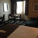Table and chairs, desk and easy chair BEST WESTERN PLUS Winnipeg Airport Hotel  |  1715 Wellingt