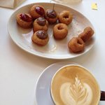 An assortment of donuts and latte.