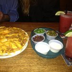 Cheese fries with toppings and margaritas.