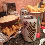 The huge fish sandwich with fries and a Ginger Beer