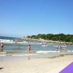 Praia  com água clara e mar muito calmo.