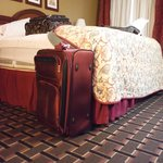 """Fullsize suitcase next to the """"King"""" bed"""