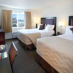 Two Queen beds with a city view includes a coffee maker, refrigerator and microwave