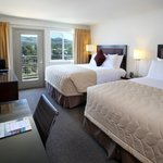 Two Queen beds with a river view includes a coffee maker, refrigerator and microwave
