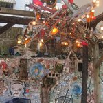 Patio sitting area with the chandelier made with a collage of recycled materials.