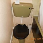 Dated bathroom and uneven toilet and cistern