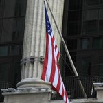 the proud american flag outside of the wall street