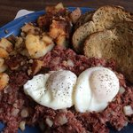 Poached eggs with corned beef hash and home fries.
