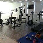 Gym with bench press, universal machine, bicycle treadmills and kettlebells.