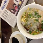 Morning paper, coffee, and noodle soup from breakfast buffet