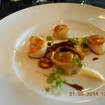 Pan seared scallops with roast onion puree, beef tortellini & a ginger reduct