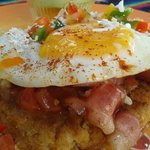 El Sol is a potato cake stuffed with cheese topped with bacon, tomato, spicy salsa and an egg.
