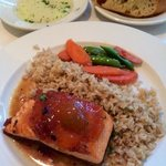 Salmon with a Ginger and Mango relish served with brown rice and vegetables. Behind a plate of d