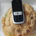 moblie phone beside a plain burger
