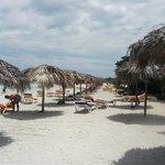 Relax on the white sandy beach alongside a clear calm sea