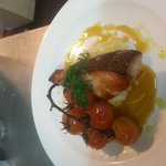 Panfried Salmon fillet , creamy garlic mash with confit vipe ripe tomatoes and a saffron burre b