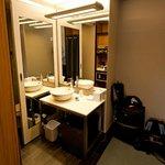 Waschbereich, links davon Dusche, im Spiegel ist der Safe und Kaffeemaschine zu sehen