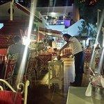 waiter cracks open a pot containing lamb stew at Baharat