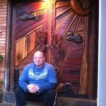 Chris (charming proprietor) sits outside gorgeous hand-carved door to the grounds.