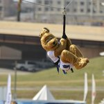 Splash, the RIVERSPORT Mascot, rides the SandRidge Sky Zip.
