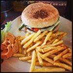 Panino con hamburger formaggio fuso e julienne di peperoni accompagnato da patatine e salsa old