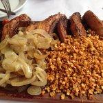 Tábua com 6 fatias de picanha, cobertas por alho frito e cebola.