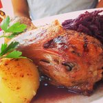 Roasted duck with potato dumpling and cabbage in beer sauce.