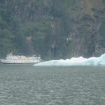 A touring boat giving cruisers a closer look at  the Tracy Arms Fjord area passes an iceberg.