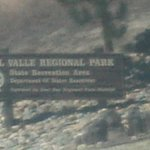 a welcoming park sign on top of the mountain going to the gate