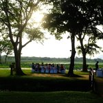 A group dining in the grounds during sunset