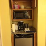 The microwave, toaster, dishes, and glasses in the room.