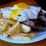 Batatas fritas, cobertas com cebolas, carne grelhada e 2 ovos fritos