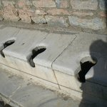 17 hole mens' potty with running water and stone seats