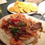 "Lomo saltado and a side of patacones (also know as ""tostones"" or fried plantains)."