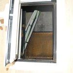 fenêtre de la salle de bain vue sur les cables électrique et les évacuations d'eau usé