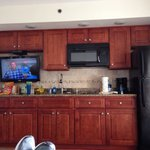 Kitchenette area as viewed from sitting in couch.  Two burner cooktop full sized fridge