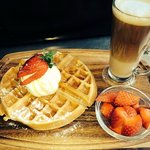 Belgian waffles topped with fresh berries and ice cream