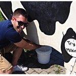 Travel Writer Brandon Sousa milking a wooden cow at Whittamore's Farm